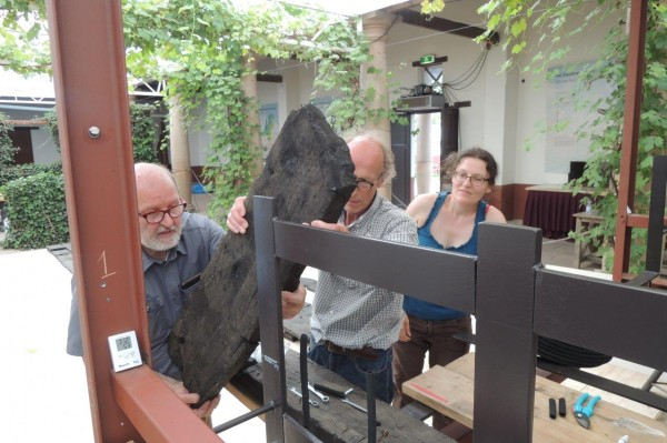 Wouter, Henny en Yardeni tillen het zware kimhout in het restauratieframe (foto: Alexander de Vos).